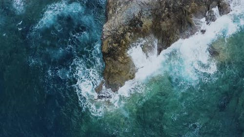 Aerial of Waves Crashing of Rocks. Flying above Turquoise Waves