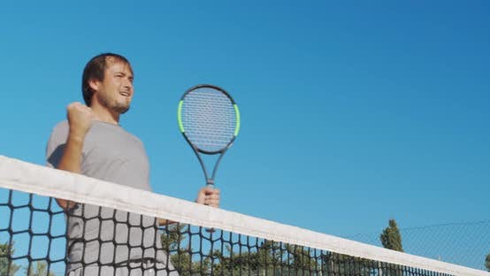 Male Athlete Playing Tennis on Outdoors Hard Court. Happy Man in Celebration of Success and Win.
