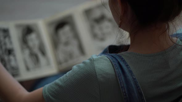 Woman Looking at Old Photo Album of Her Family
