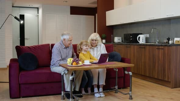 Thumbnail for Grandfather and Grandmother Sitting in Living Room and Teaching Small Granddaughter Using Laptop
