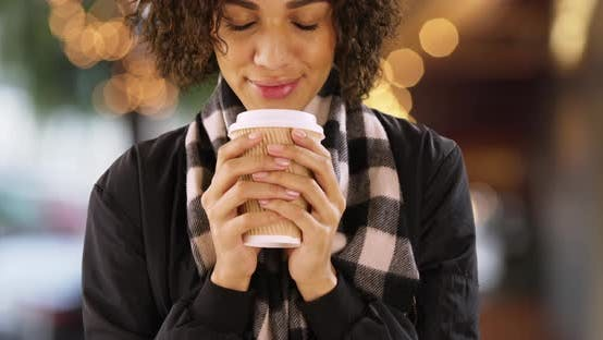 Thumbnail for Cute African woman holding coffee cup outdoors, holding paper cup.
