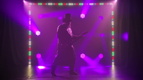Thumbnail for A Silhouette of a Rock Guitarist in a Black Hat and Cloak Performs on Stage and Performs a Solo