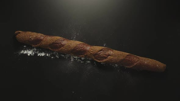 Thumbnail for Brown Rye Baguette Falling Down On A Black Surface