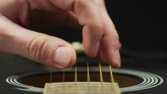 Thumbnail for Extreme close up of fingers strumming strings