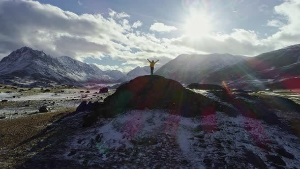 Cover Image for Male mountain climber raising hands with icepick on top of snowy peak. hiker at the top of a rock wi