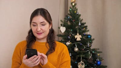 Beautiful Woman with Phone on Background of Christmas Tree