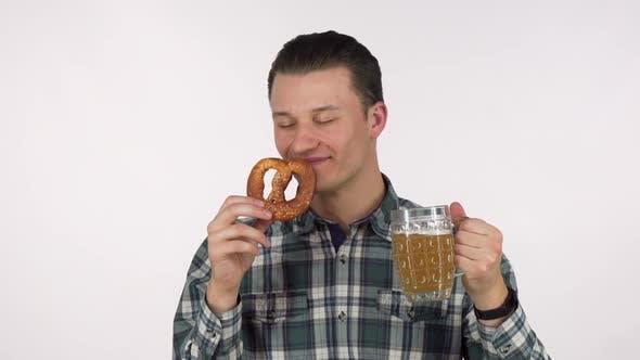 Thumbnail for Fröhlicher junger Mann hält Becher Bier riechend köstliche Brezel