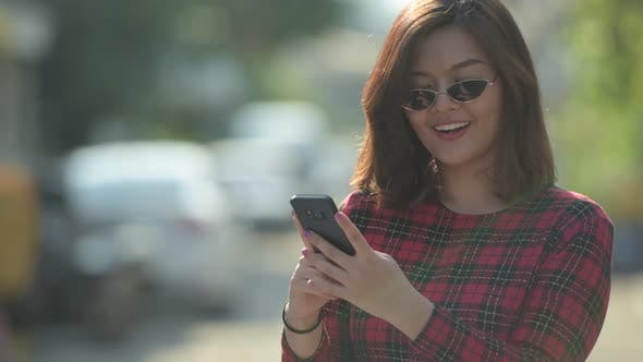 Thumbnail for Happy Young Beautiful Asian Businesswoman Thinking While Using Phone Outdoors