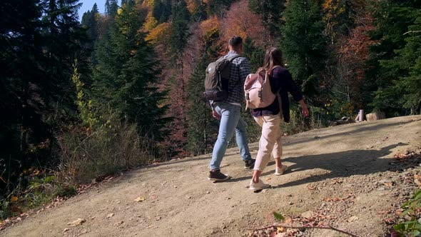Young Backpackers in Autumn Wood