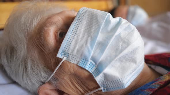 Thumbnail for Portrait of Granny Wearing Medical Protective Mask From Virus. Sick Lady with Sad Sight Looking Into