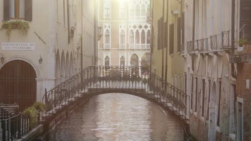 Arch bridge between buildings over narrow channel, beautiful architecture around