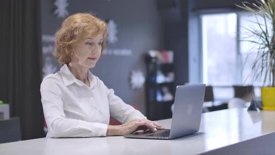Thumbnail for Portrait of Middle Aged Caucasian Woman Typing on Laptop Keyboard, Looking at Camera and Smiling