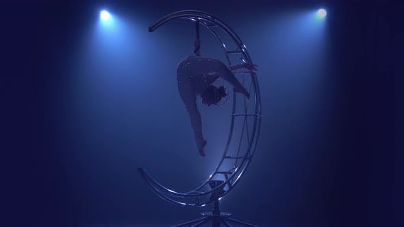 Thumbnail for Rhythmic Gymnastics Girl Performs the Scum on One Arm in the Air on a Metal Rotating Structure Moon