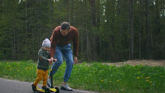 Thumbnail for In Slow Motion, a Young Happy Father Teaches His 2-Year-old Son To Ride a Scooter in a Park on a