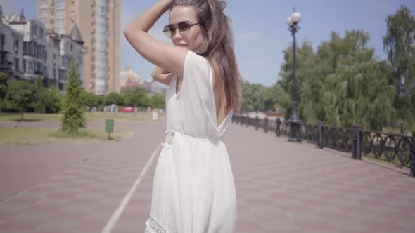 Thumbnail for Cute Young Girl Wearing Sunglasses and a Long White Summer Fashion Dress Walking Outdoors. Leisure