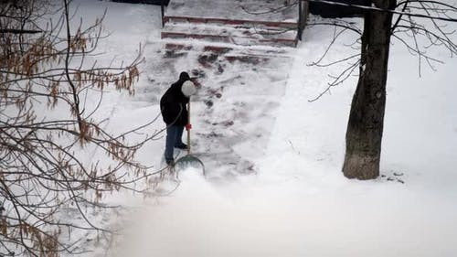 Person Cleans Snow From Sidewalk To House with Large Shovel