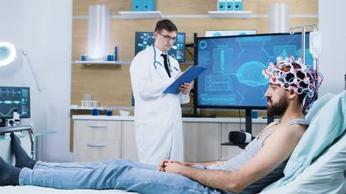 Doctor Analysing Patient Sitting on Bed and Wearing Brain Scanning Device