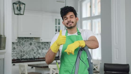 Professional Cleaner in Uniform Standing with Vacuum Cleaner in front of Camera