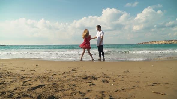 Thumbnail for Young Guy with Beautiful Girl in Pretty Summer Dress on Vacation By the Ocean Dancing and Gently
