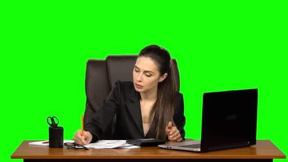 Thumbnail for Business Woman Works at a Laptop, Compares Data with Counts on a Calculator, and Makes Entries in