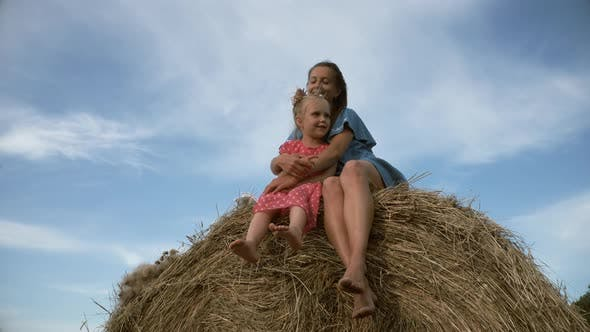 Thumbnail for Young woman with daugter sitting on haystack