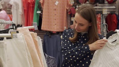 Woman Chooses Clothes in a Shopping Center or Clothing Store
