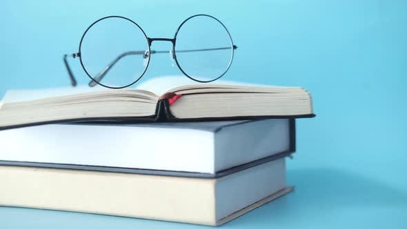 Open Book Mug Eyeglass and a Pencil on Wooden Table