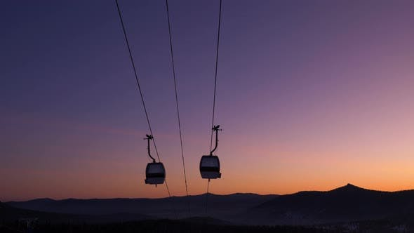 Silhouettes of Ski Lift Cabins Moving at Resort at Sunset