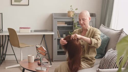 Hairless Woman Putting on Wig at Home