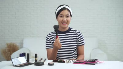 Beauty blogger present beauty cosmetics while sitting in front camera for recording video.