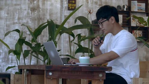 Young Teenager Man in Glasses a Teenager of Asian Appearance Black, Working on a Laptop Smokes a