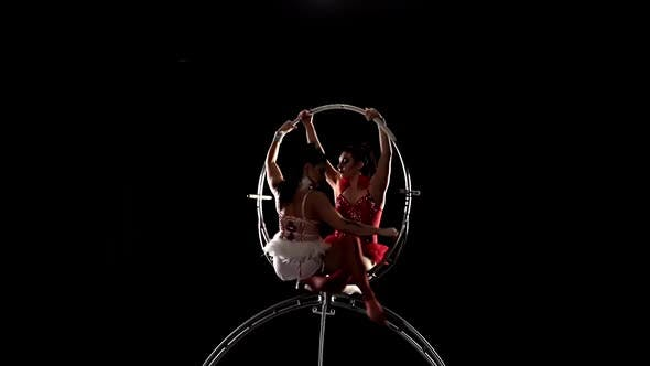Thumbnail for Gymnasts Performs a Trick in the Aerial Hoop. Black Background. Slow Motion