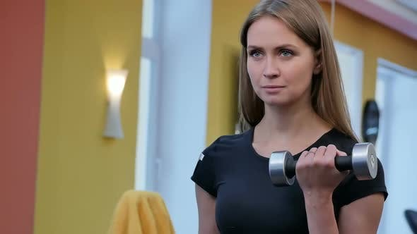 Thumbnail for Young Woman Working Out with Dumbbells at the Gym