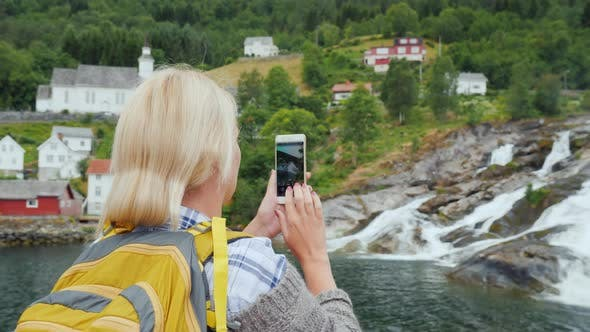 Cover Image for Traveler Photographs a Picturesque Landscape in Norway, a Waterfall and Traditional Norwegian Houses