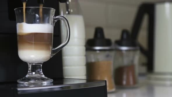 Thumbnail for Cappuccino From the Coffee Machine Is Poured Into a Glass Cup