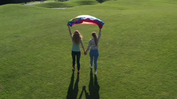 Thumbnail for Drone View of Gay Couple Walking with Rainbow Flag