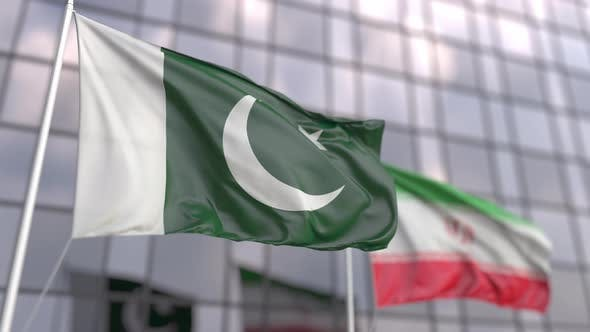 Waving Flags of Pakistan and Iran in Front of a Skyscraper