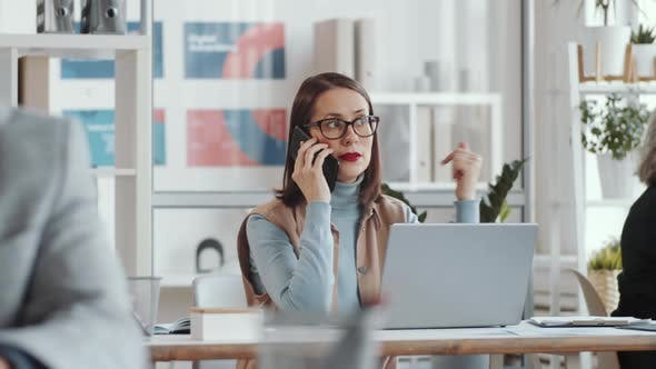 Thumbnail for Businesswoman Talking on Phone at Desk in Open Space Office