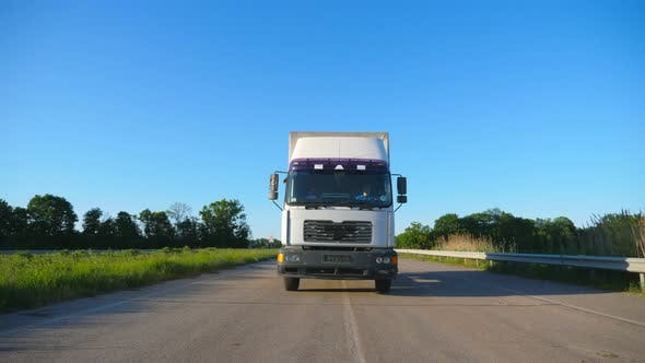 Thumbnail for Front View of Truck with Cargo Trailer Driving on Highway Transporting Goods at Summer Day