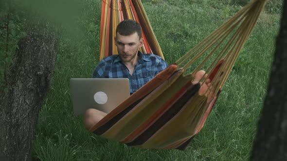 Man relaxing with laptop in hammock in summer holidays. Male freelancer lying in hammock outdoors
