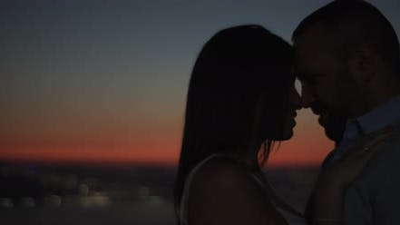 Thumbnail for Silhouette of a couple standing close to each other, smiling, feeling happy