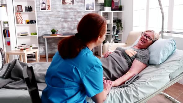 Female Health Care Taker Holding Old Woman Lying on Hospital Bed