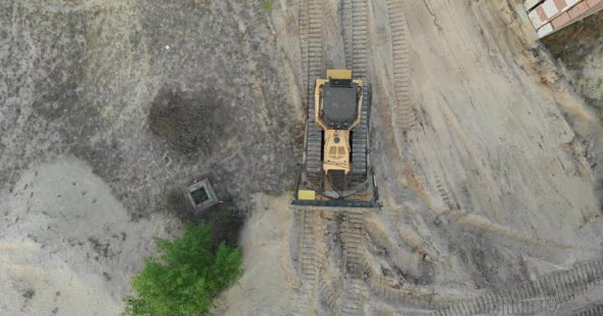 Top Aerial View on Tracked Bulldozer Rides on Sandy Road at Construction Site