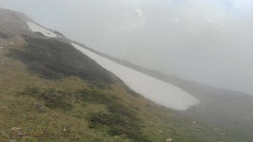 Piece of Snow on the Mountain Slope In Fog