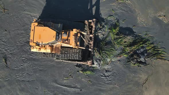 Aerial View on Top Large Bulldozer Cleans the Bottom of the Lake From Thickets and Swamps