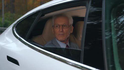 a Man Rides with an Open Window Sitting in the Back Seat of a Car