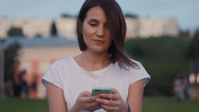 Beautiful Young Woman Typing on Phone Outdoors