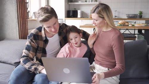 Glückliche junge Eltern und Kind Kind Tochter mit Laptop sitzen zu Hause auf der Couch