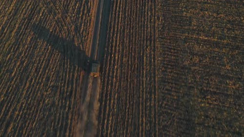 Aerial Shot of Farmer Jeep Riding Along Empty Rural Road Among Field. Off Road Vehicle Speeding on