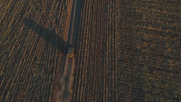 Thumbnail for Aerial Shot of Farmer Jeep Riding Along Empty Rural Road Among Field. Off Road Vehicle Speeding on